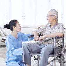 elderly man on wheelchair and staff smiling