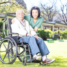 elderly man on wheelchair and caregiver smiling
